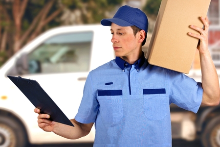package delivery: Handsome young delivery man carrying carton box.