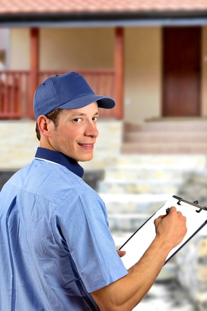 consign: Delivery man with his schedule, in front of house.