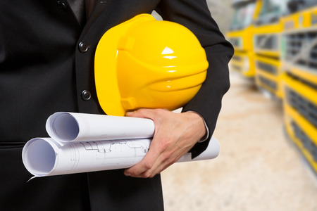 architecture plans: Close up of an architect hand holding project documents and hat. Stock Photo