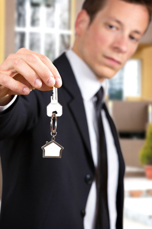 front house: Young businessman giving house keys, in front of a house.