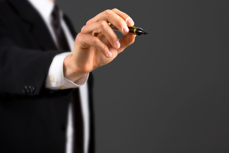 Close up of business dressed male hand holding marker,isolated on dark background. photo
