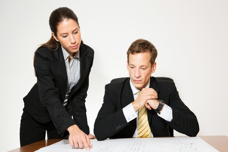 businees: Business dressed man and woman working at the office desk. Stock Photo