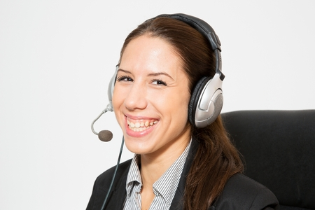 telemarketer: Young business dressed female, sitting in chair, working as telemarketer.