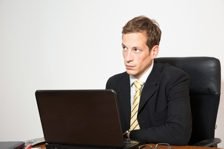 chief executive officers: Young business dressed male sitting at desk and working on laptop.