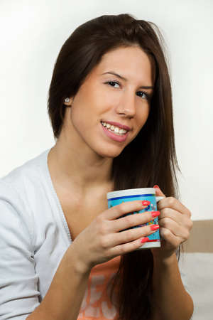 studding: Cute young woman,drinking hot tea.