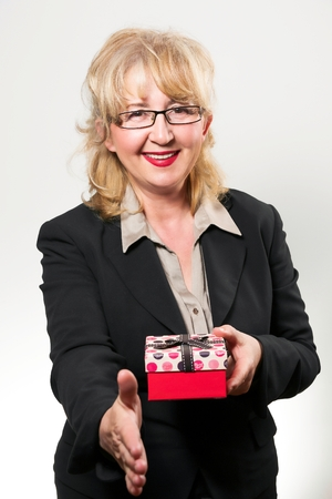 Portrait of a middle aged businesswoman, smiling with present in hands. photo