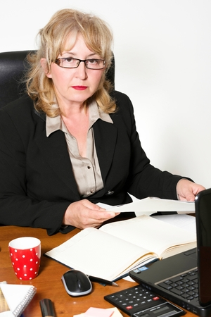 Middle aged businesswoman, at the desk in the office. photo