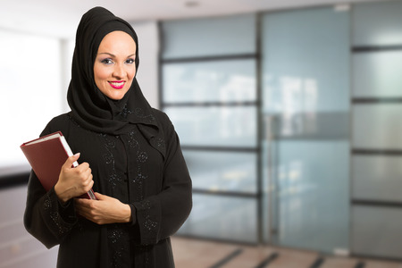 arabic woman: Arabic woman in traditional dressed, standing in front of the office.