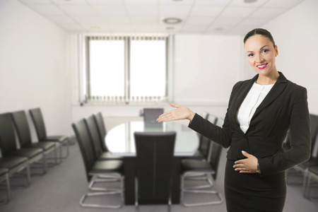 Business dressed woman standing in conference room, smiling.