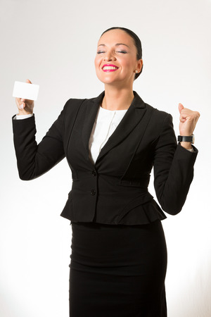 Business dressed woman with white card in hand, smiling. Stock fotó