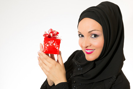 Model dressed in traditional Arabic style, holding red present.