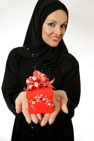 arabic woman: Arabic young woman dressed in abaya,holding a present and smiling to the camera. Stock Photo