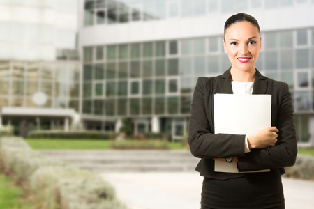 building backgrounds: Business dressed woman with folder, standing in front of the building. Stock Photo