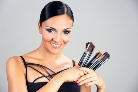Beautiful smiling black woman girl holding makeup brushes. Standard-Bild
