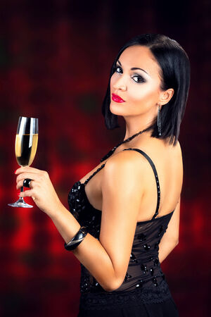Beautiful black hair woman holding glass of champagne, against dark red background. photo