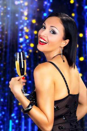 Attractive black hair woman drinking champagne, against shiny blue background. photo