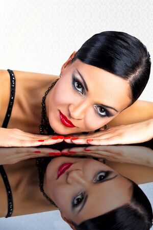 Beautiful black hair woman,lying on reflective table. photo