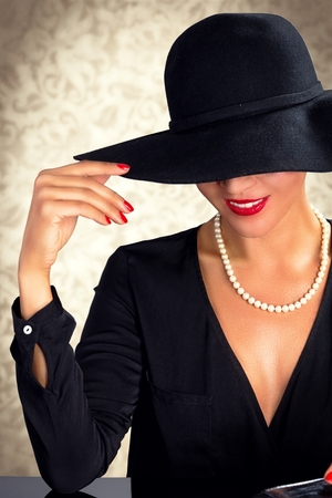 Attractive woman wearing black dress, hat and pearls, sitting on black table. Stock Photo