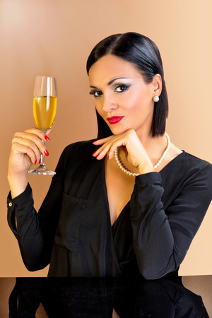 Beautiful black hair woman sitting at the table and holding glass of champagne. photo