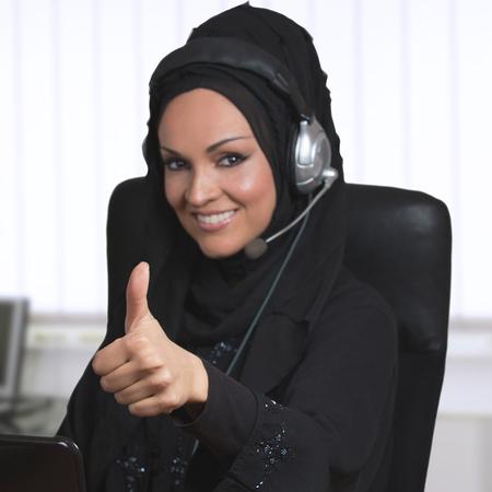 arabic woman: Arabic woman, traditional dressed, working as a customer service representative.