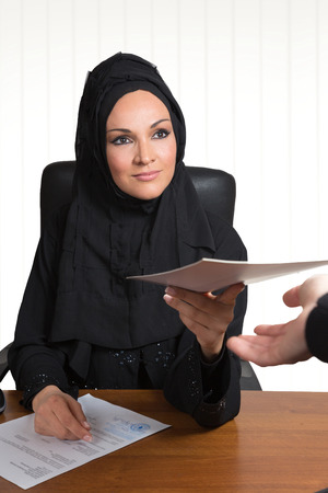 learning arabic: Arabic business woman,handing over a contract,inside office space. Stock Photo