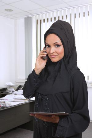 fille arabe: Arabe femme d'affaires, de parler au téléphone, à l'intérieur de son bureau.