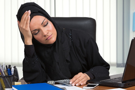 dissapointed: Dissapointed arabic woman, traditional dressed, working at desk, inside her office.