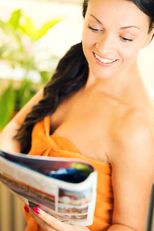 fullness: Beautiful young woman, with towel on body, reading magazine.