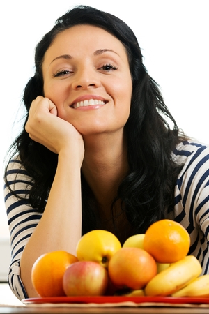 fullness: Pretty young woman, smiling in front of the fruit basket Stock Photo