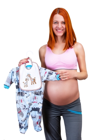 cm: Happy pregnant woman, holding boys dress, isolated on white background. Stock Photo