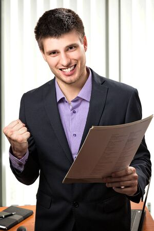 suited up: Happy young business man inside his office. Stock Photo