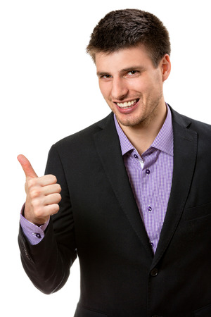 suited up: Positive young business man,showing thumb up. Stock Photo