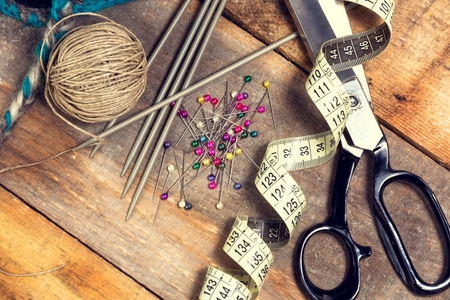 sewing supplies: Sewing kit. Scissors, bobbins with thread, measure tape and needles on top of the old wooden table.