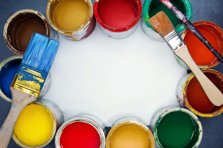 Colorful paint cans, brushes and empty space for note. Zdjęcie Seryjne