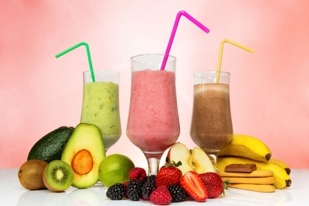 bannana: Smoothie concept. Fruit smoothies in different colors next to various fruits.