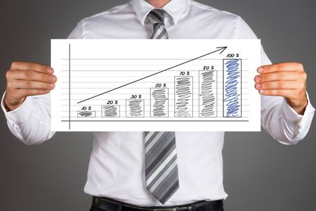 successes: Successes concept. Businessman holding paper with growing columns business graph. Stock Photo