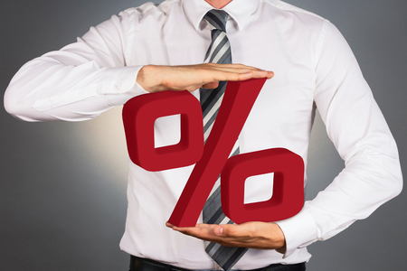 mortgage rates: Adult businessman holding 3 D percent sign isolated on dark background.
