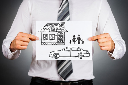 Close up of a business manholding white card with housecar and family drawing inside.Isolated against grey background.