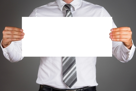 Business man holding a blank white board isolated on dark gray background.