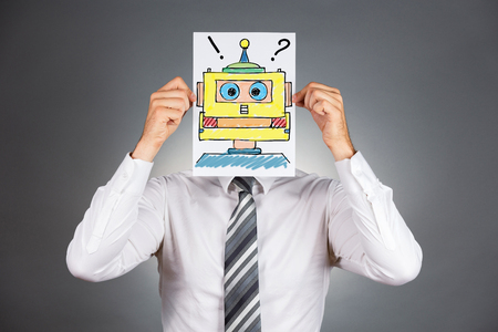 mundane: Portrait of a businessman holding a drawing of a colorful robot head in front of his face.Isolated on grey background. Stock Photo