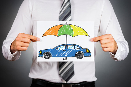 Car insurance concept. Businessman holding withe paper with drawn colorful car under safety umbrella.