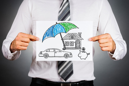 caja fuerte: Concepto de seguro de vida. El hombre de negocios que sostiene el papel con el dibujo de un coche casa y dinero símbolos bajo el paraguas.