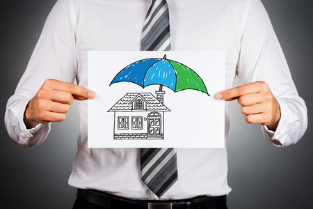 insurance: Home insurance concept. Businessman holding paper with drawing of a house under the umbrella. Stock Photo