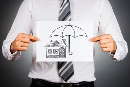 seguro: Concepto de seguro de hogar. El hombre de negocios que sostiene el papel con el dibujo blanco y negro de una casa bajo el paraguas.