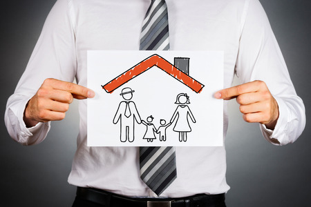 Family and home insurance concept. Businessman holding paper with drawing of a family inside family home.