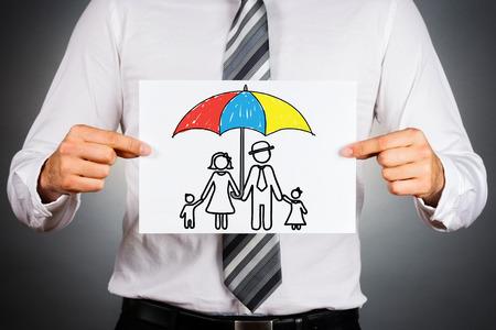 seguro: Concepto de seguro de la familia. El hombre de negocios que sostiene el papel con el dibujo de una familia bajo el paraguas. Foto de archivo