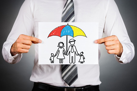 Family insurance concept. Businessman holding paper with drawing of a family under the umbrella. Archivio Fotografico