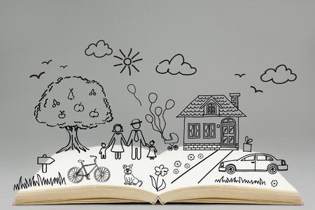 persona leyendo: Concepto de familia feliz. Gráfico de la familia en la parte superior del libro abierto. Casa, automóvil, bicicleta, árbol, hierba, flores, perro, nubes, sol, los pájaros. Foto de archivo