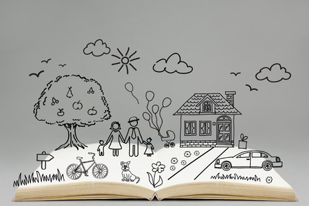 family on grass: Happy family concept. Family drawing on top of the open book. Home, car, bicycle, tree, grass, flowers, dog, clouds, sun, birds. Stock Photo