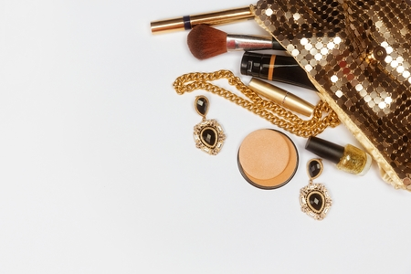 Golden woman accessories. Make up pieces, jewelry and shiny purse. Top view. Stock Photo
